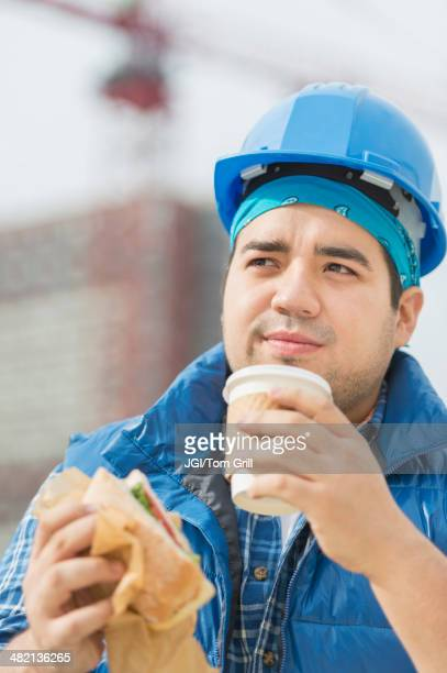 Mixed race worker eating lunch on construction site