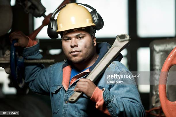 Mixed race worker in hard-hat holding large wrench