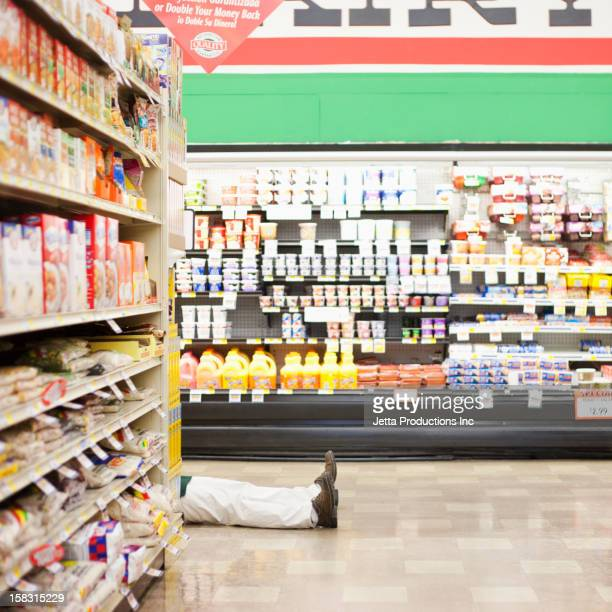 Mixed race worker laying on floor in grocery store