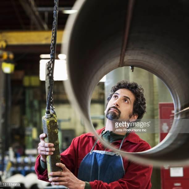 Gemischtes worker in Fabrik lifting-pipe