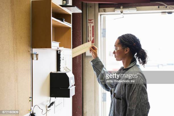 Mixed Race worker selecting time card in factory