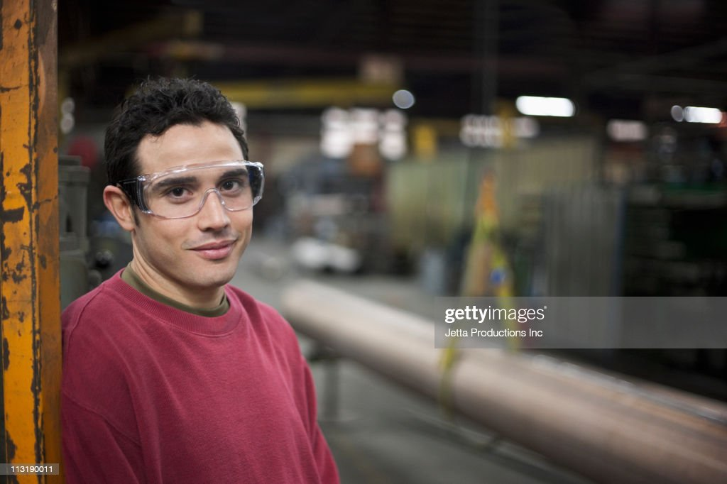 Mixed race worker standing in factory : Stock Photo
