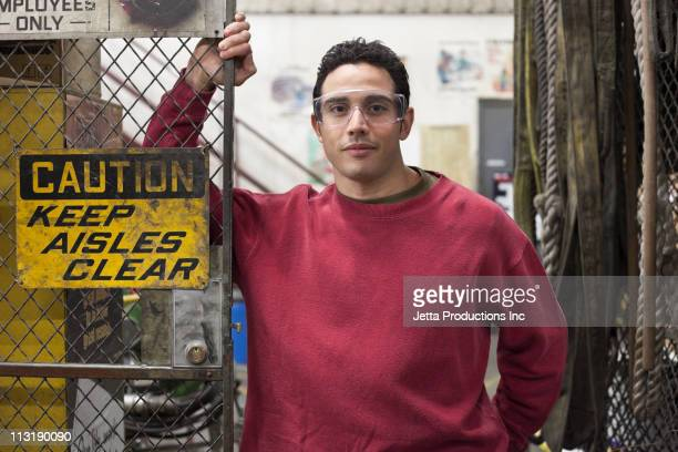 Mixed Race worker standing near fence in factory