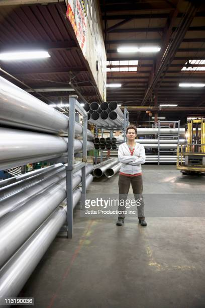 Mixed race worker standing near metal pipes in factory
