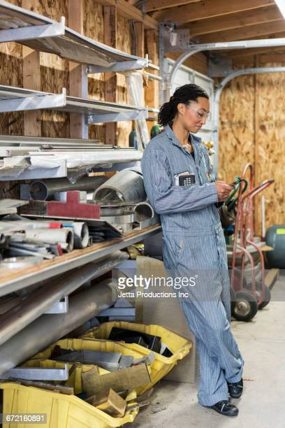 Mixed Race worker texting on cell phone in factory