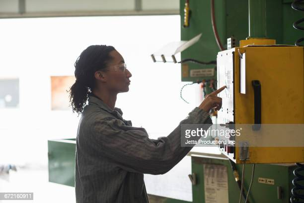 Mixed Race worker using control panel in factory
