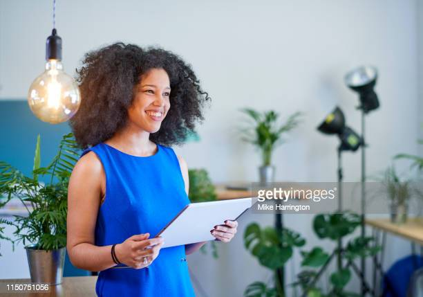 mixed race young female working in sustainable creative office with ipad - sleeveless dress stock pictures, royalty-free photos & images