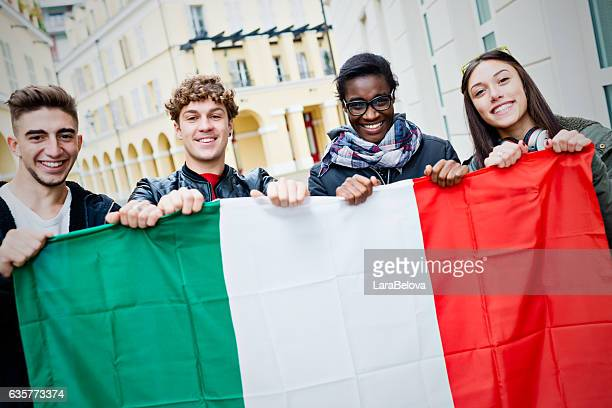 mixed race young friends holding italian flag - bandiera foto e immagini stock