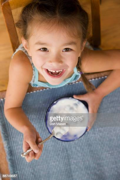 Mixed race young girl eating yogurt with spoon