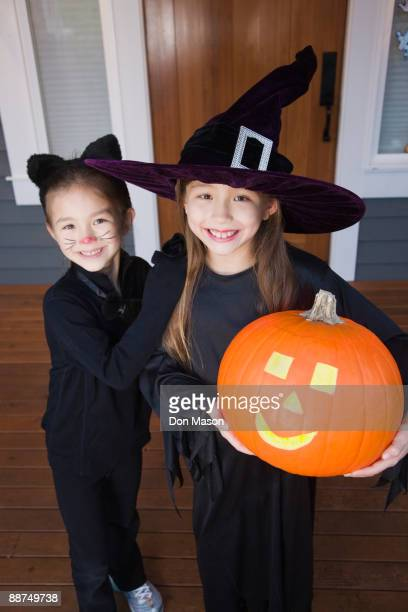 mixed race young girls in cat and witch costumes - cat costume stock photos and pictures