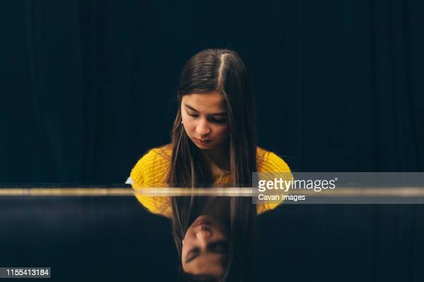 mixed race young woman is sitting behind piano in a concert hall. - length stock pictures, royalty-free photos & images
