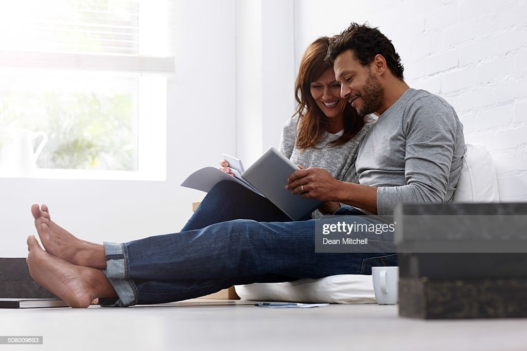Mixed raced couple calculating their expenses : Stock Photo