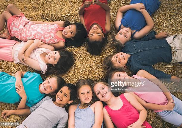 Enfants de race mixte groupe de mentir en cercle sur la paille