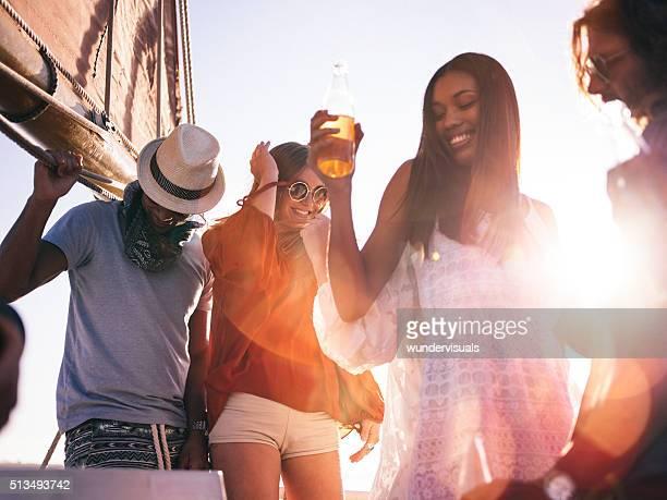 Groupe de race mixte amis appréciant un Yacht fête au coucher du soleil