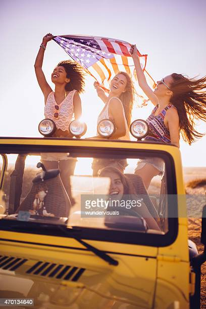 Mixed racial group of girls happily flying an American flag