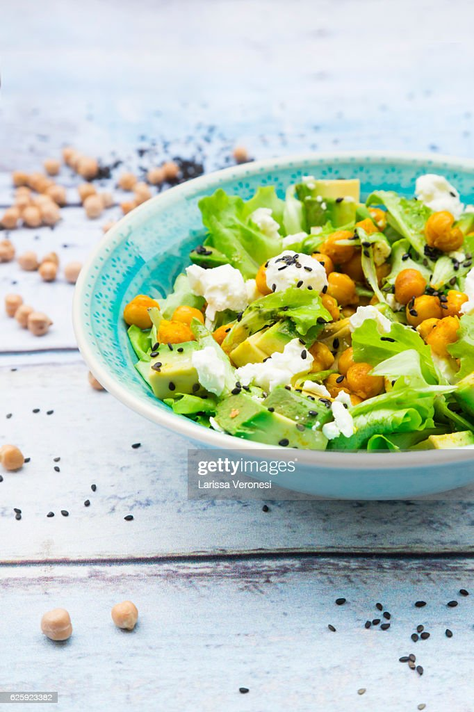 Mixed raw salad with roasted chickpeas, feta cheese, avocado and black sesame on plate : Stock-Foto