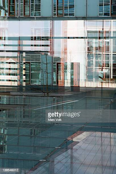 Mixed reflections on glass floor and walls of Jakob Kaiser Haus