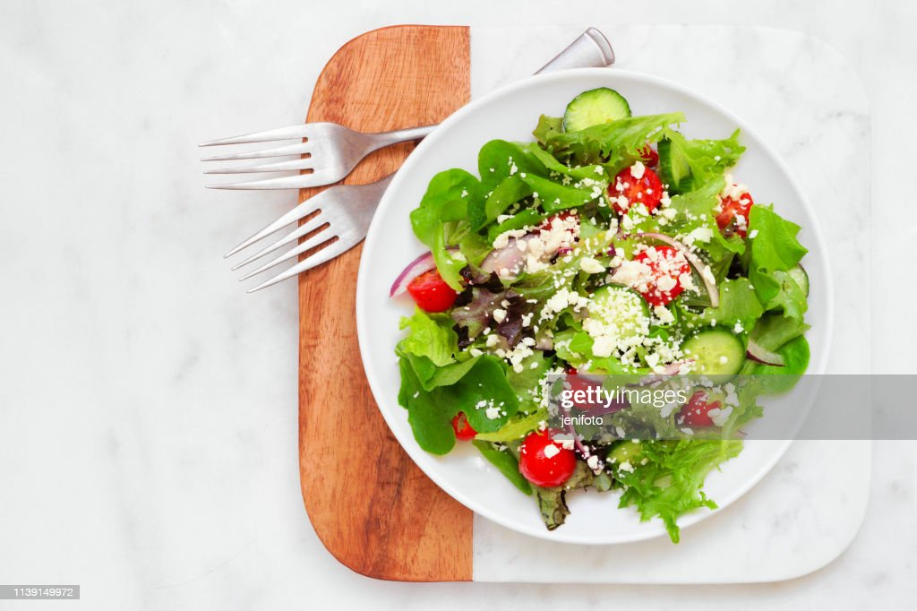 Mixed salad top view on a marble and wood serving board : Stock Photo