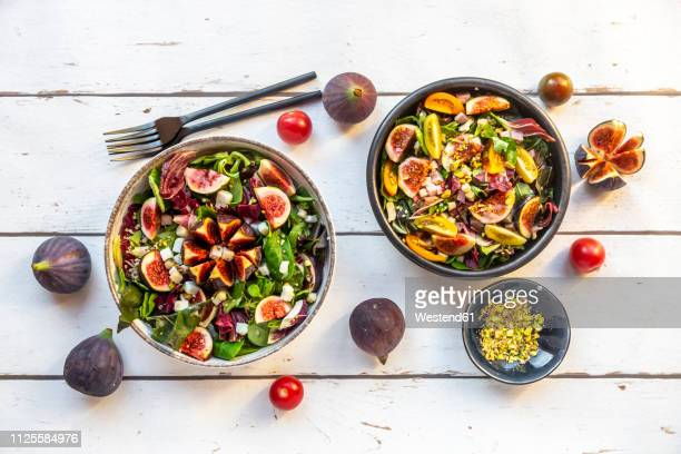 mixed salad with fig, tomato, ham, cheese, pistachio - tropical fruit stock pictures, royalty-free photos & images