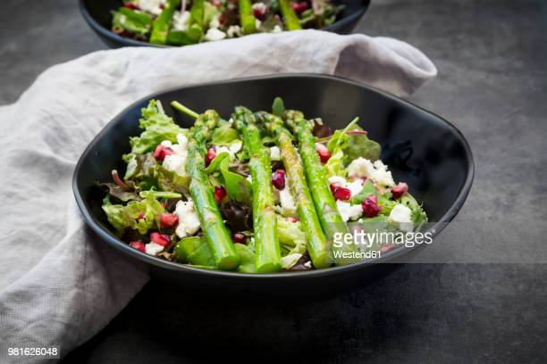 mixed salad with fried green asparagus, feta and pomegranate seeds - asparagus stock pictures, royalty-free photos & images