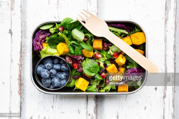 mixed salad with roasted tofu, red cabbage, pomegranate seeds, blueberries and curcuma in lunch box - meal stock pictures, royalty-free photos & images