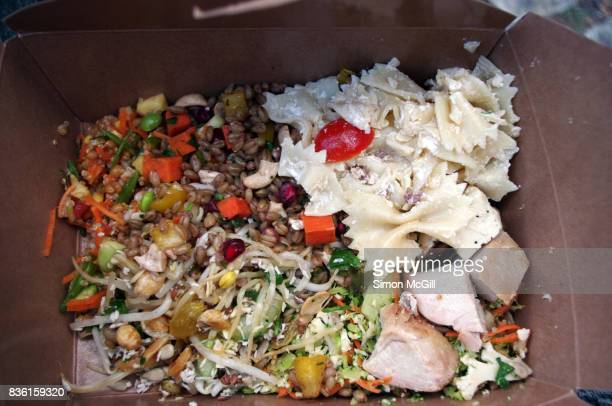 Mixed salads of grains, nuts, fruit, pasta and vegetables in a brown cardboard take out box