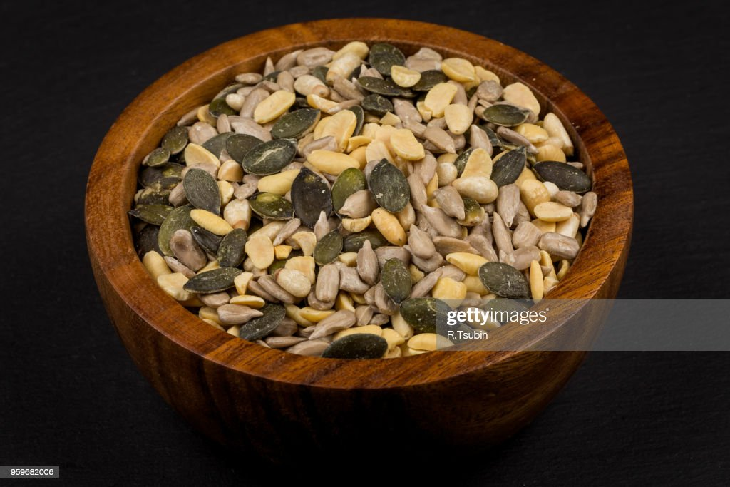 mixed seeds and nuts in wooden bowl on dark background : Stock-Foto