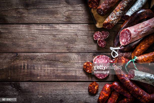 Mixed spanish chorizo pieces border on rustic wooden table