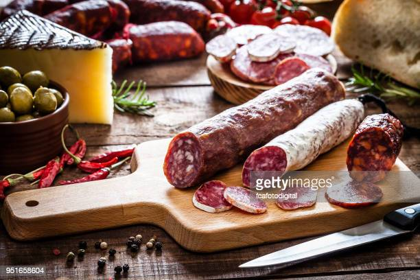 Mixed spanish chorizo pieces on rustic wooden table