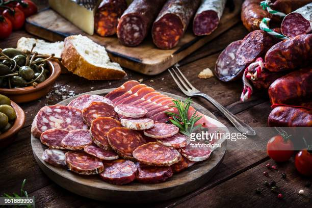 mixed spanish chorizo slices plate on rustic wooden table - chorizo stock pictures, royalty-free photos & images