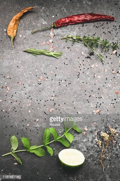 gemischte gewürze und kräuter auf schwarzem stein tisch ansicht - gewürz stock-fotos und bilder