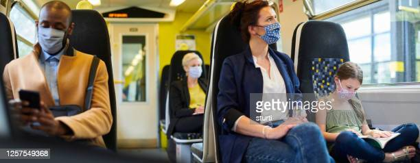 mixed use train passengers wearing masks - commuter stock pictures, royalty-free photos & images