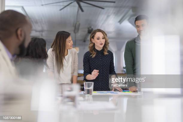 a mixed-ethnic group of business colleagues sign paperwork at the conference table - società foto e immagini stock