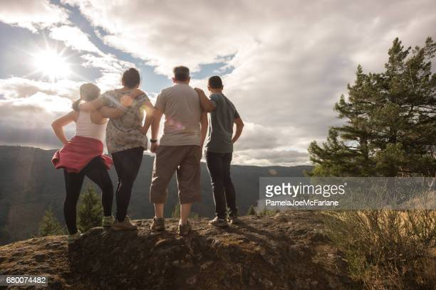 Mixed-Ethnic Hiking Family Enjoying View from Mountain Summit in Wilderness