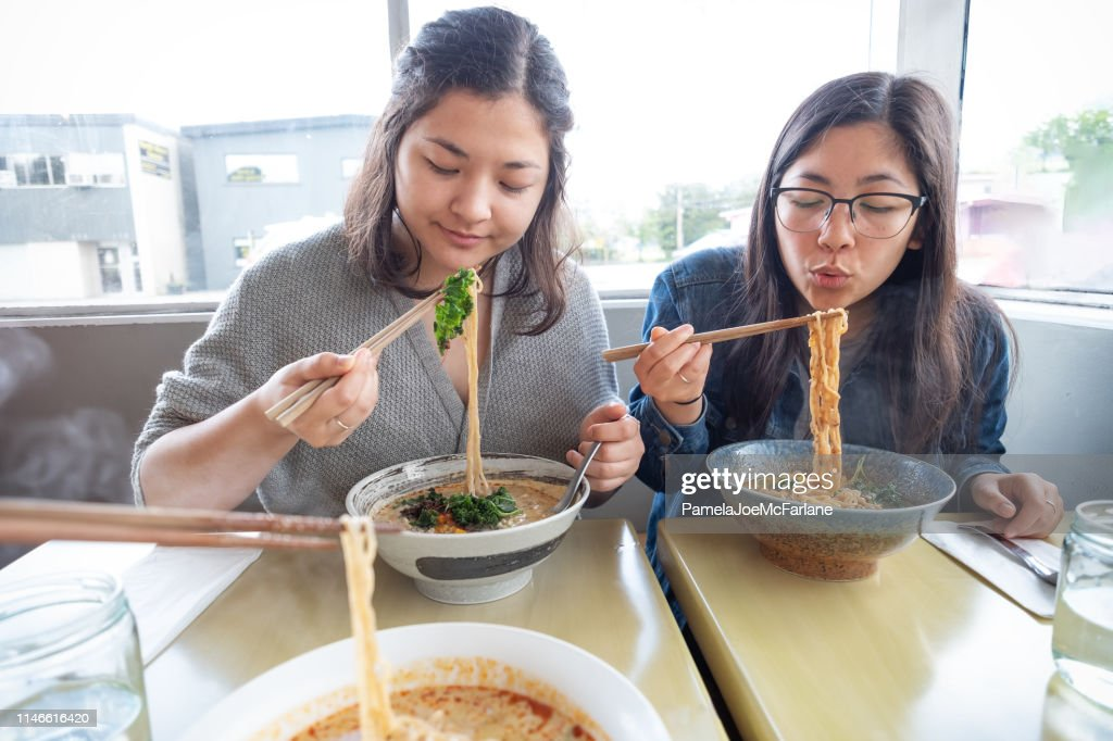 POV, Mixed-Ethnic Sisters Eating Vegan Japanese Ramen Noodle Soup in Diner : Stock Photo