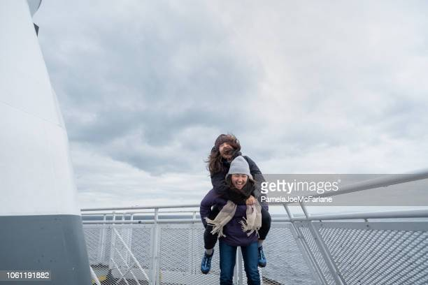 mixed-ethnic teen sisters having fun piggy backing on ferry deck - ferry stock pictures, royalty-free photos & images