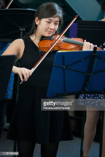 Mixed-Ethnic Teenaged Girl on Stage Playing Violin in Concert