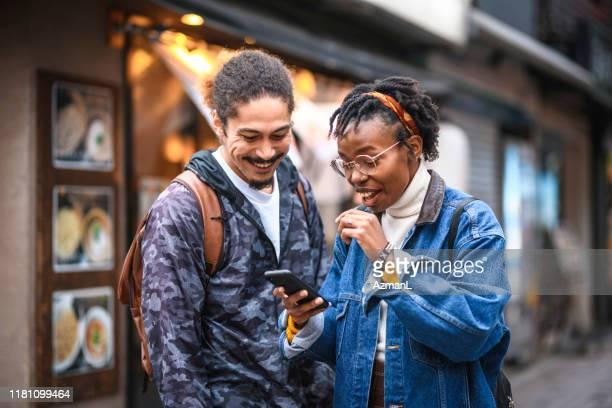 東京でスマートフォンのヘルプを取得する混合民族の休暇者 - 観光客 ストックフォトと画像