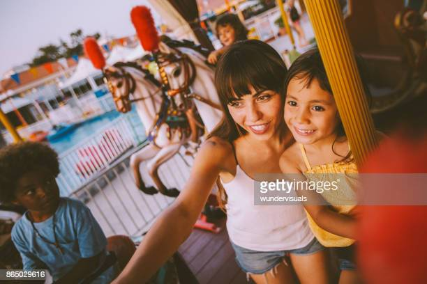 Mixed-race daughter and mother having fun on funfair carousel ride
