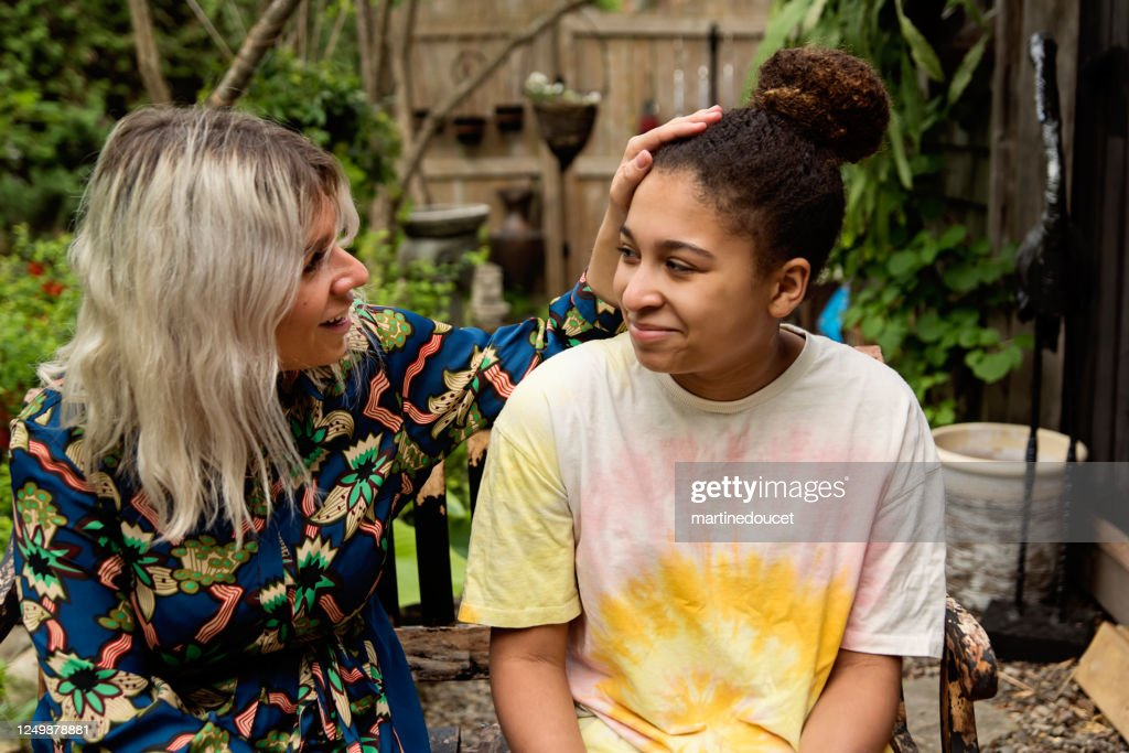 Mixed-race daughter and mother portrait in backyard. : Stock Photo