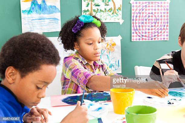 Mixed-race, elementary students in art class. Painting with watercolors