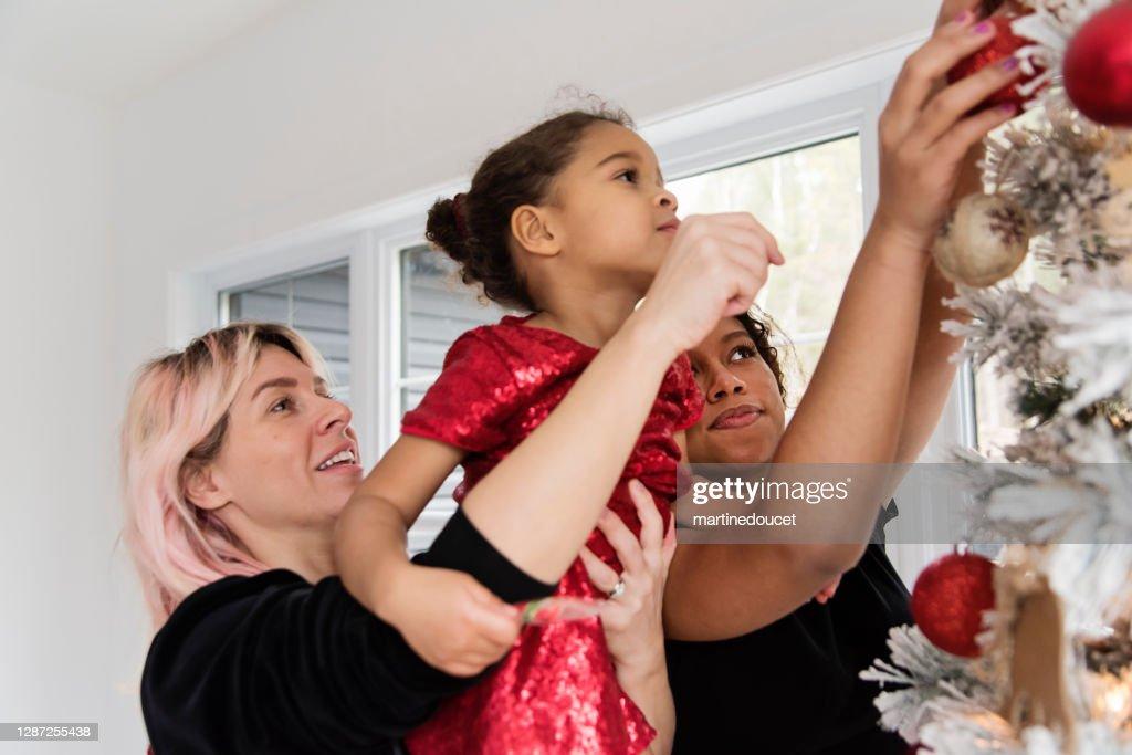 Mixed-race family decorating the Christmas tree. : Stock Photo