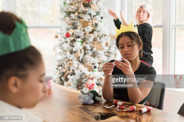 """mixed-race family decorating the christmas tree. - """"martine doucet"""" or martinedoucet stock pictures, royalty-free photos & images"""