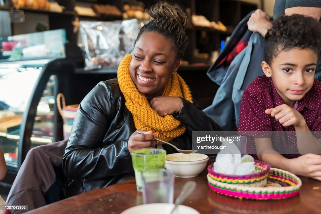 Mixed-race family eating in restaurant in winter. : Stock Photo