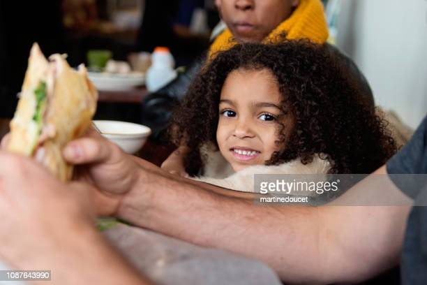 Mixed-race family eating in restaurant in winter.