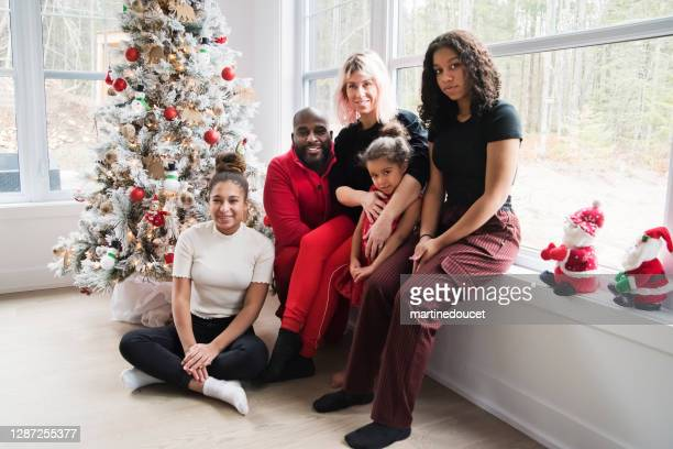 "mixed-race family portrait in front of christmas tree. - ""martine doucet"" or martinedoucet stock pictures, royalty-free photos & images"
