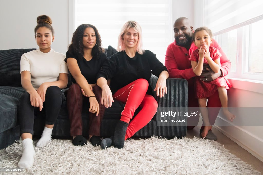 Mixed-race family portrait in living room. : Stock Photo