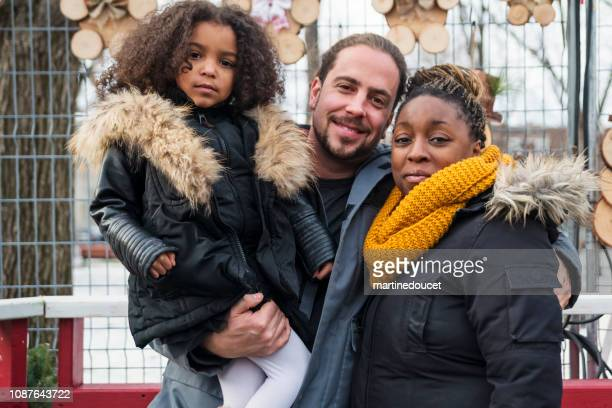 Mixed-race family portrait on city street in winter.