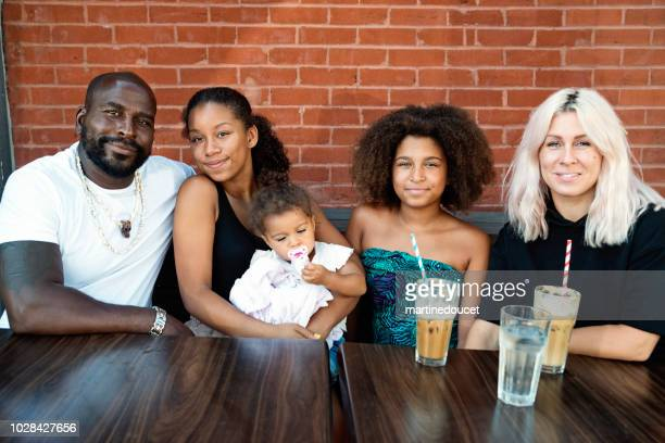 Mixed-race family portrait outdoors on a brick wall.
