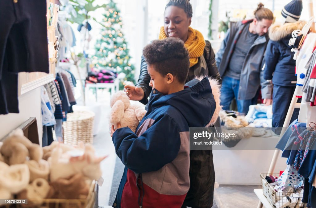 Mixed-race family shopping in children store in winter. : Stock Photo
